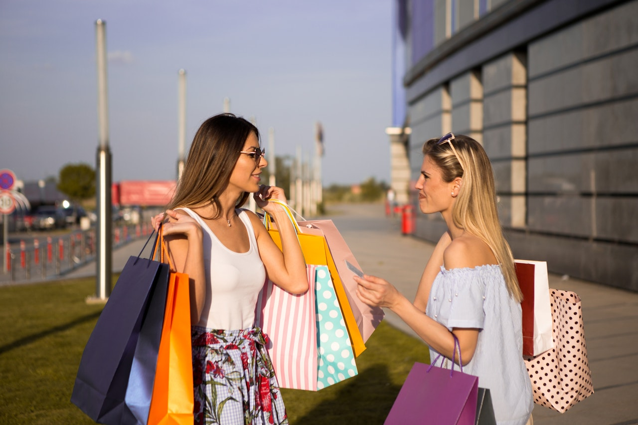 two women holding paper bags after shopping